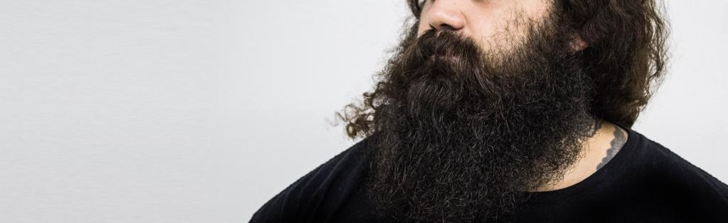 Homem com barba muito grande e bem cuidada com produtos de qualidade